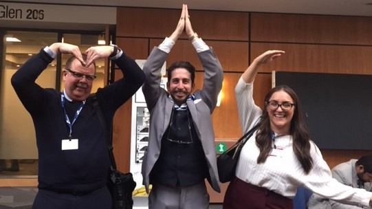 Rick Exkert, Andre Abilio and Danika Nicoletti spell out MIC